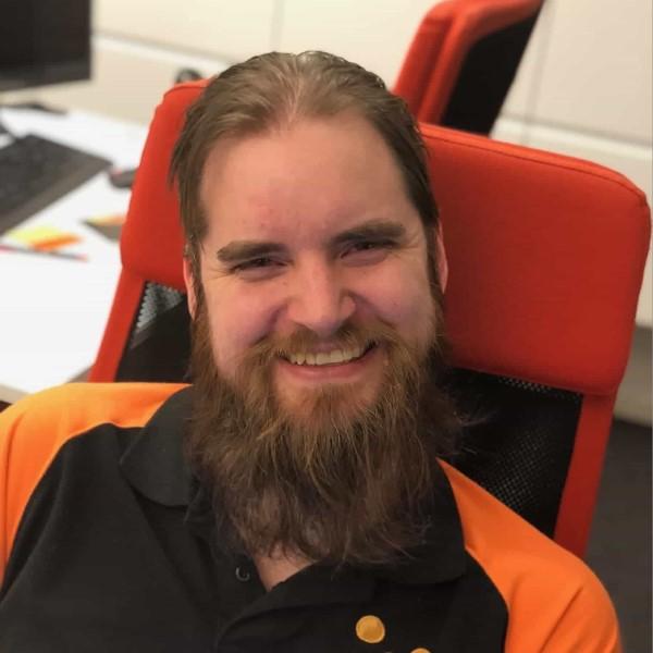 Niklas ler sittandes i stol