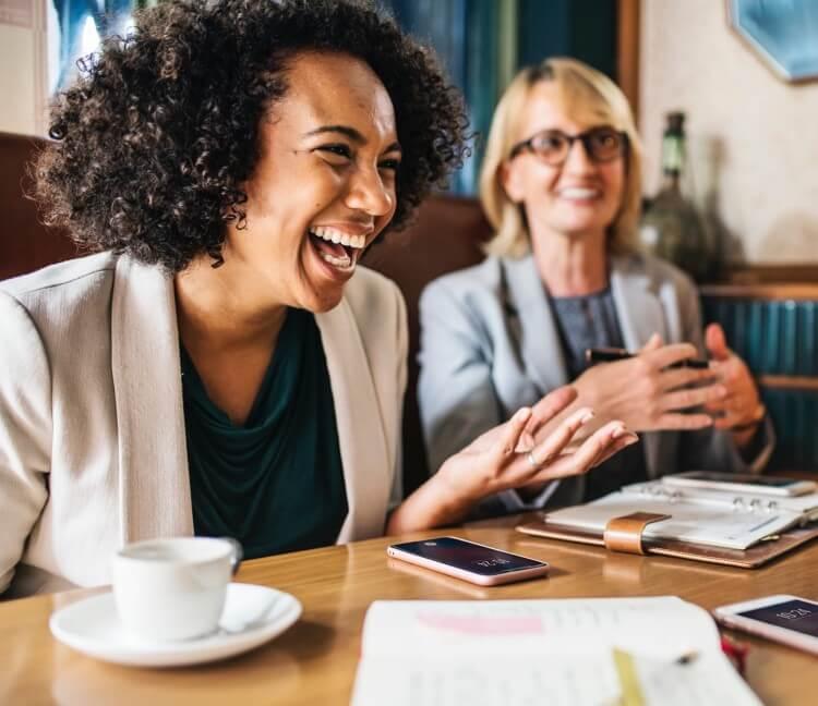Två kvinnor som skrattar över kaffe
